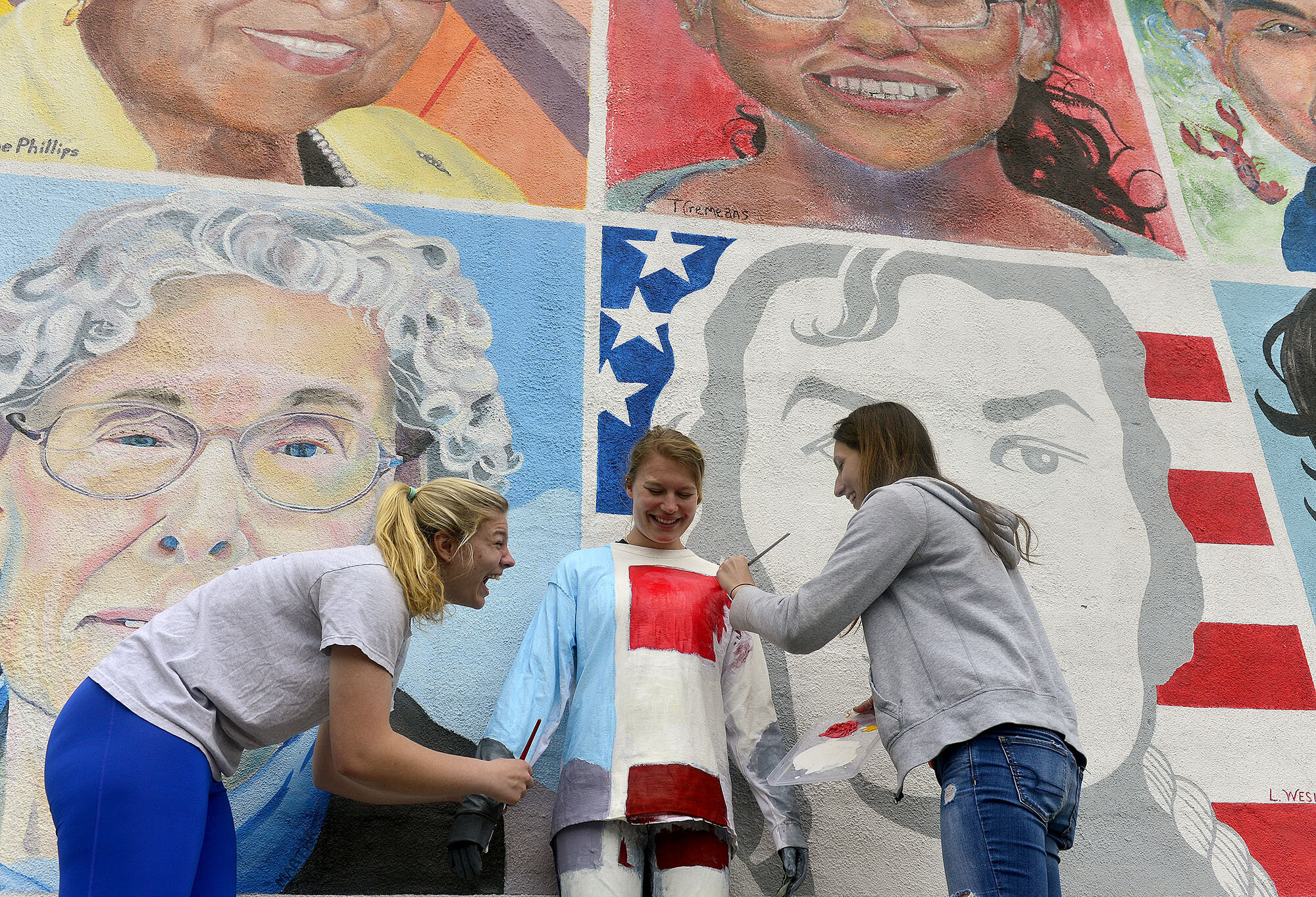 """Connecticut College sophomores Emily Ehler, right, and Emily Senatore, left, laugh as they paint classmate Caitlyn Teare, center, into the """"One Place Many Cultures"""" mural on Friday, May 12, 2017, as part of their final for a color theory class """"Decoding Color"""" in downtown New London. For their final project class members worked in teams to find an urban space and camouflage a classmate into the environment. (The Day)"""