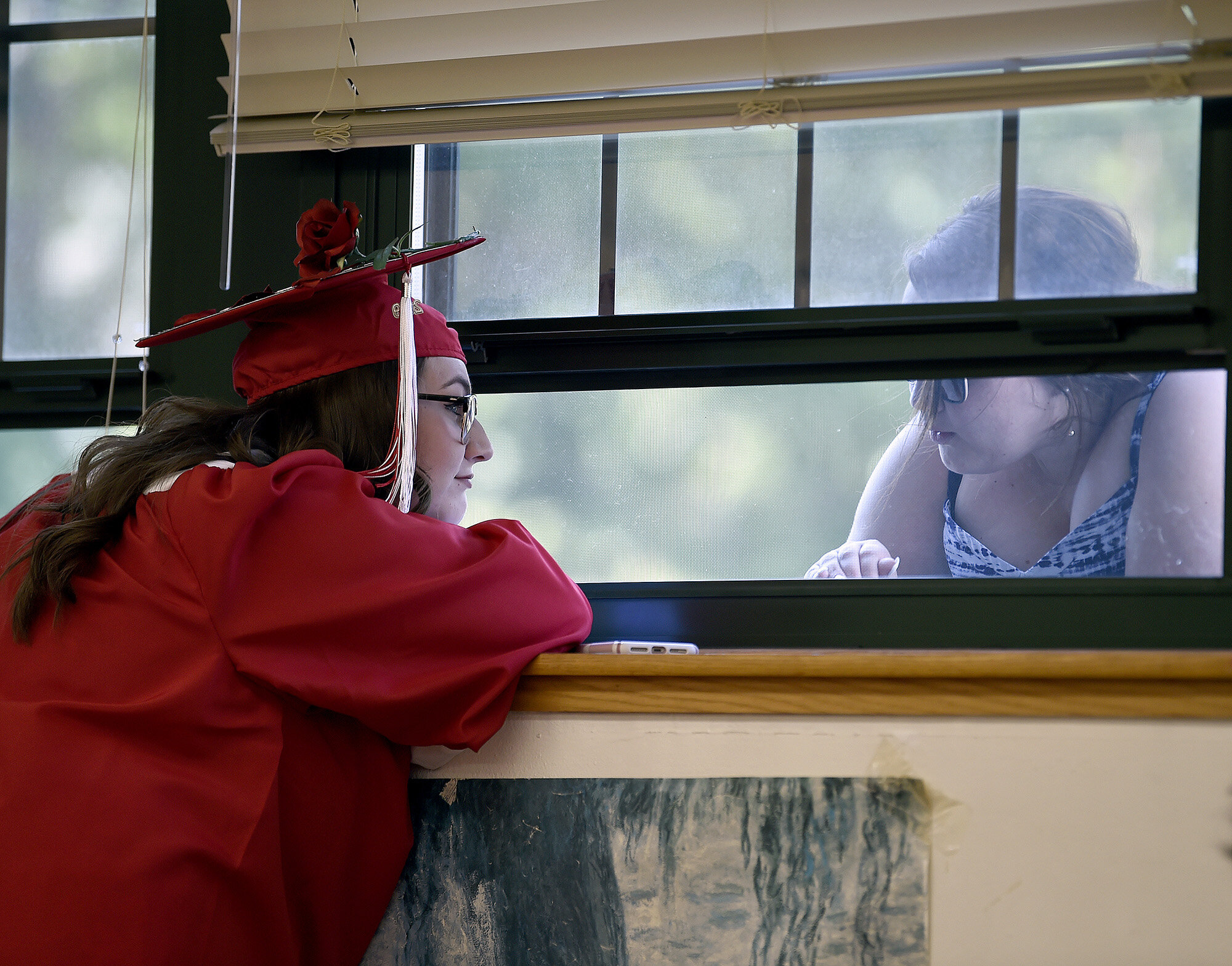 Graduate Abby Bargnesi, left, talks to her sister Taylor through a window before Norwich Free Academy's Commencement Ceremony on Wednesday, June 12, 2019. (The Day)