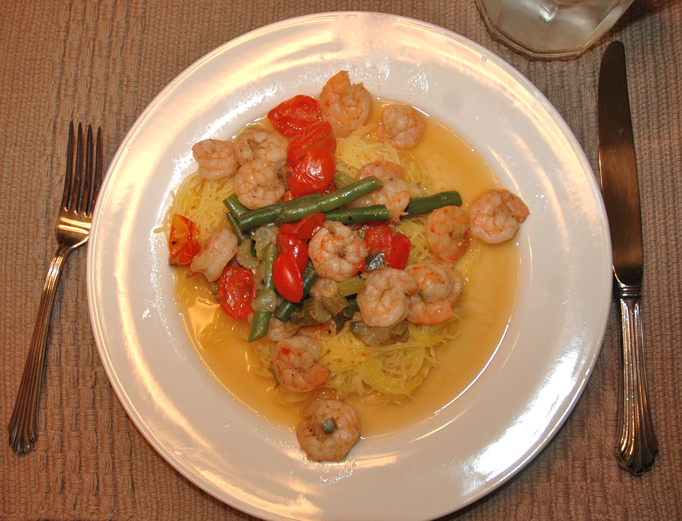 Shrimp on a set of spaghetti squash and veggies in clarified butter sauce.
