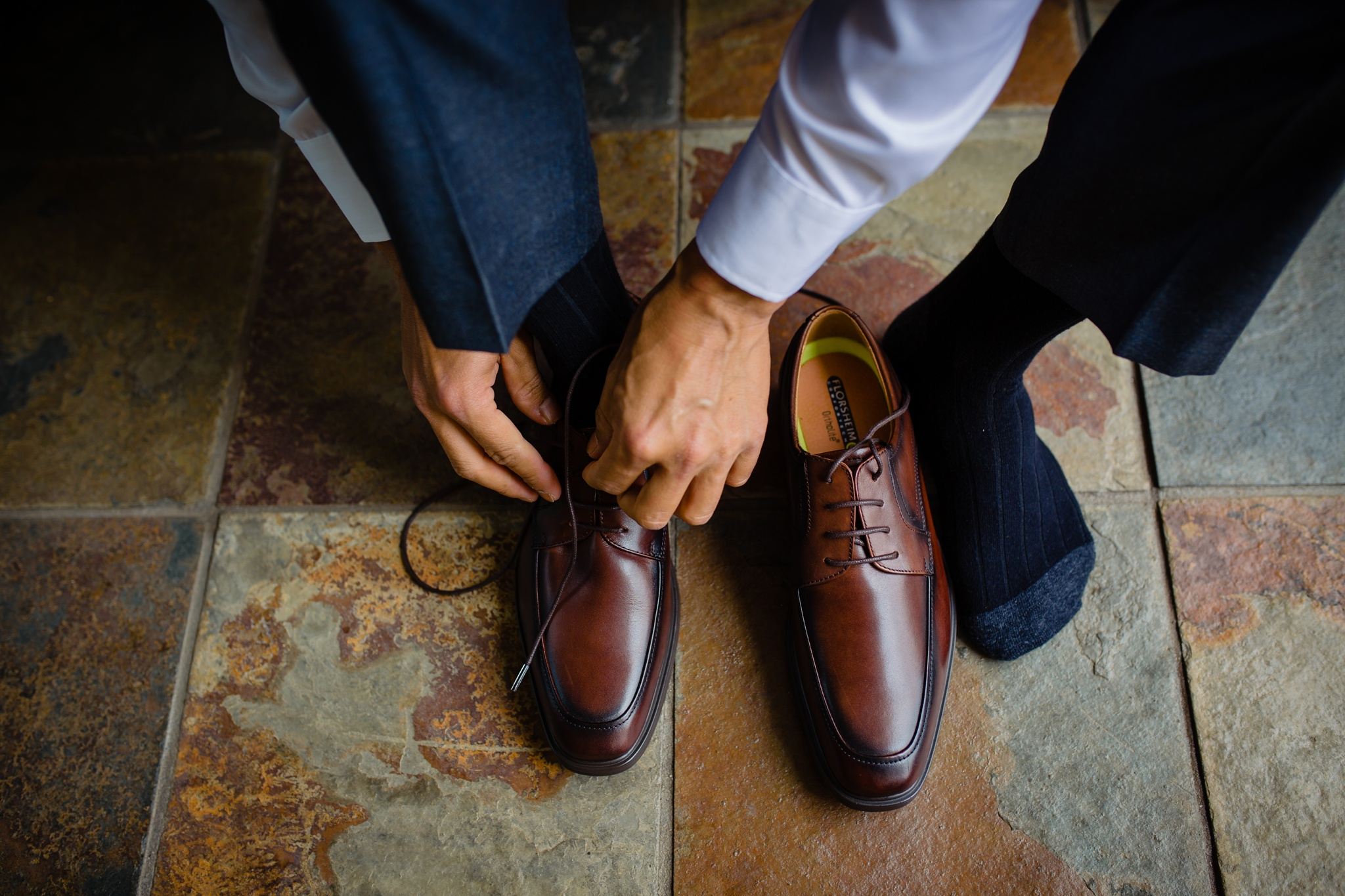 groom putting on his shoes at his wedding day at the westin hapuna