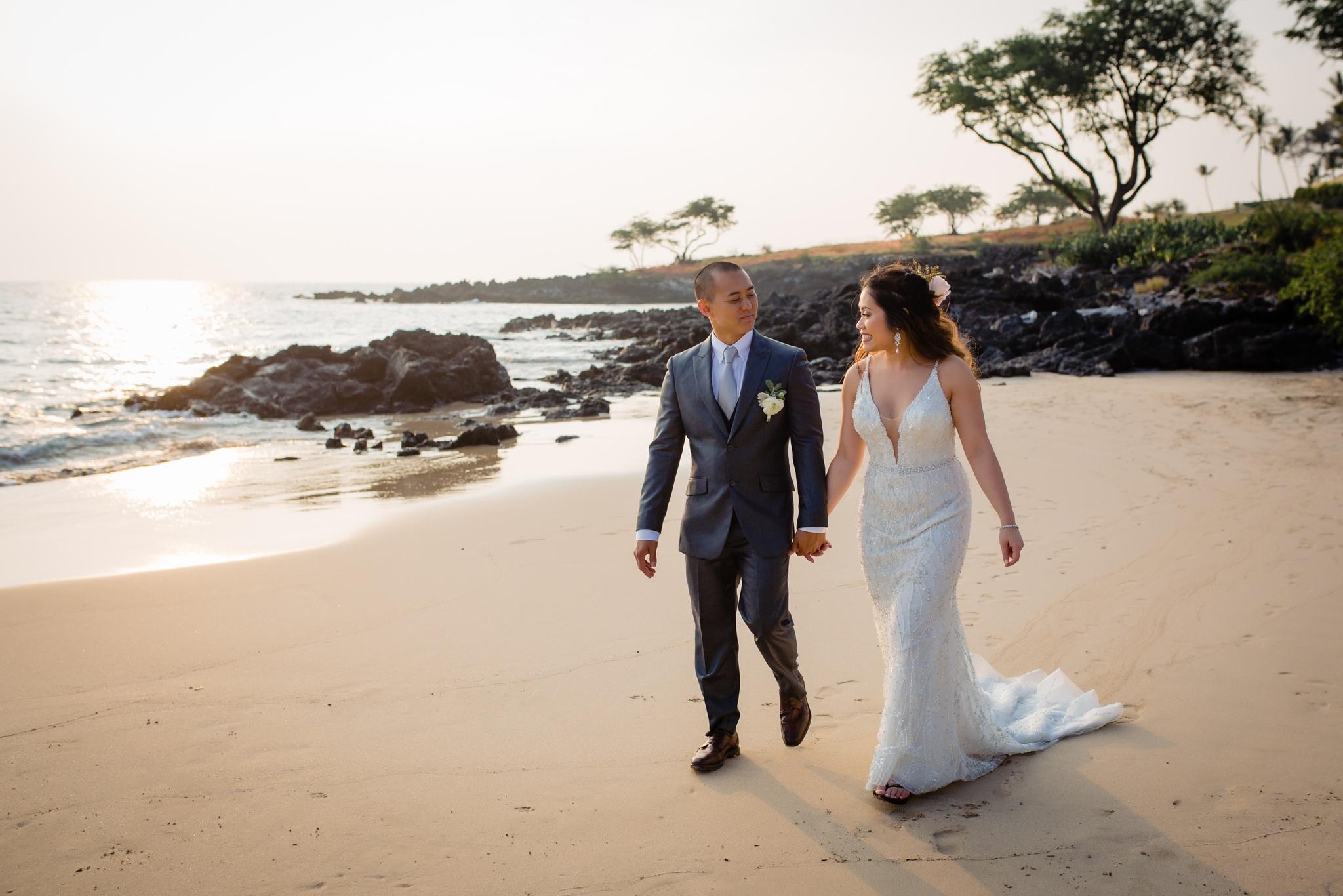 wedding couple walking hand in hand on sandy beach in hawaii