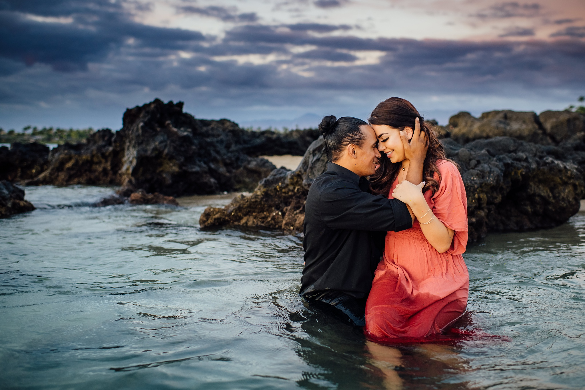engaged couple cuddling in hawaii waters