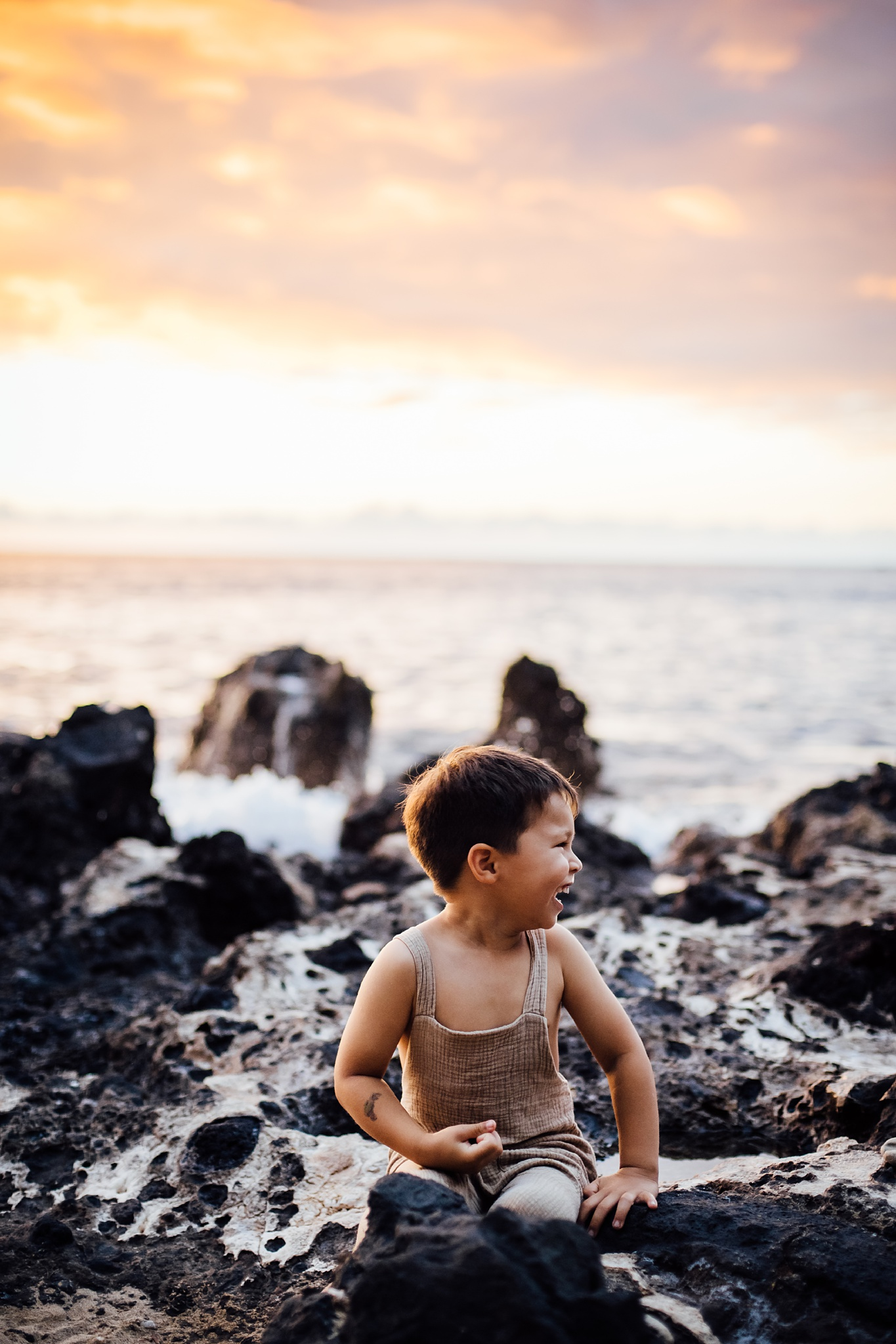 Boy playing on lava rocks during family session in hawaii
