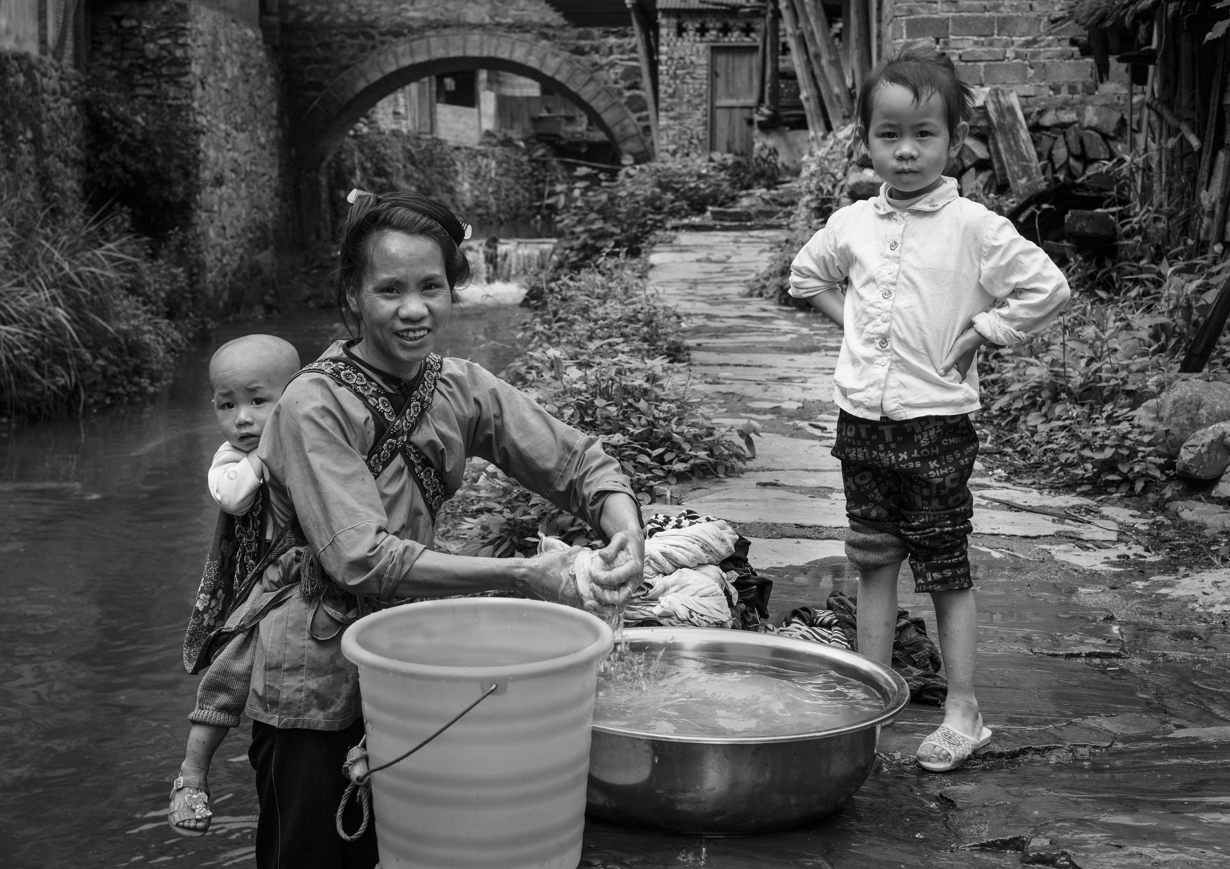 Yan aged 30 washes the families clothing in the stream near her home