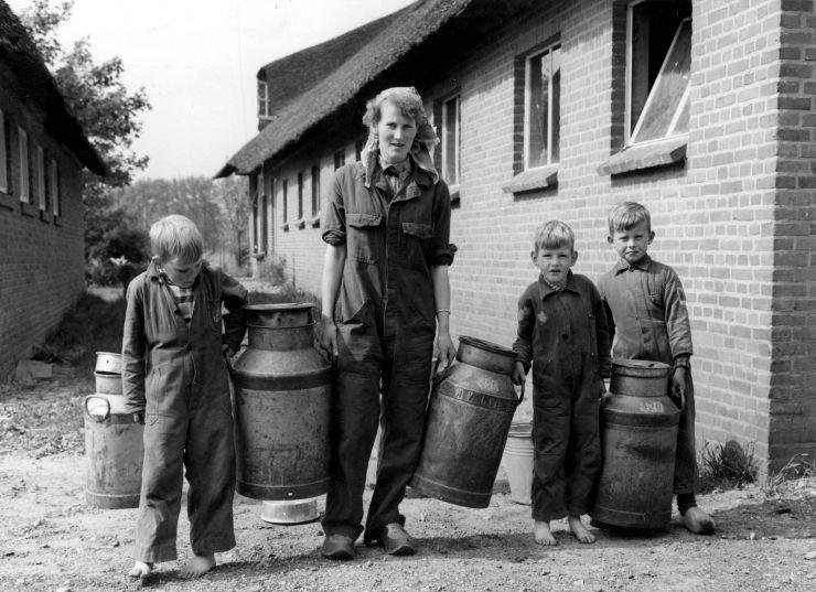 Op de boerderij. Gezinsbedrijf. Moeder en kinderen in overall met melkbussen. Nederland, [ Doornspijk], 1957 of eerder.
