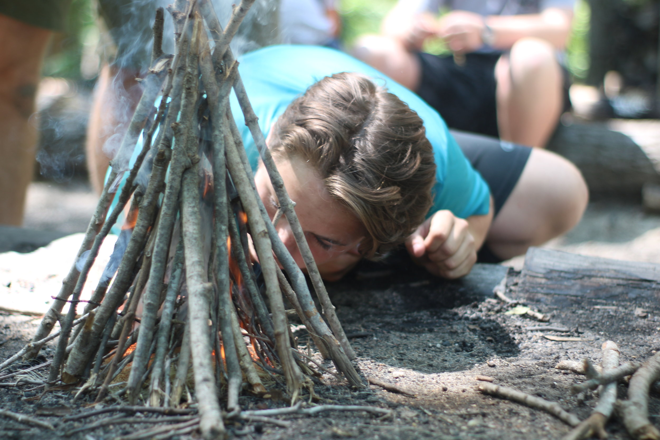 A Scout works on his 15 minute fire for the rank of Woodsman.