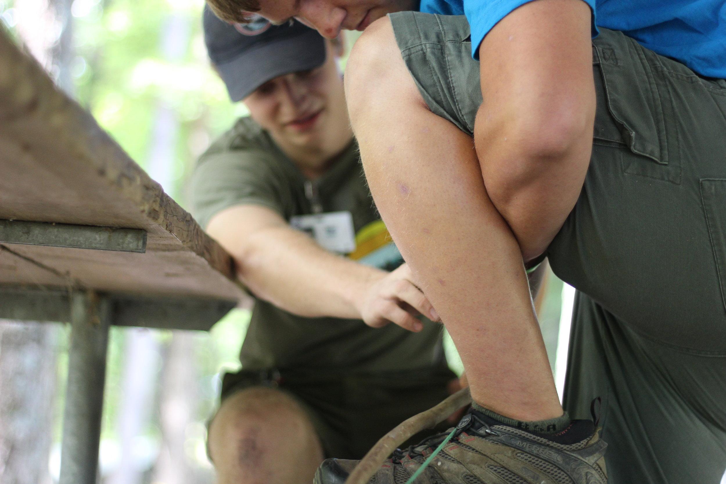 Firecrafter Director Matt Hustel helps a camper pop his spark at the firecrafter shelter.