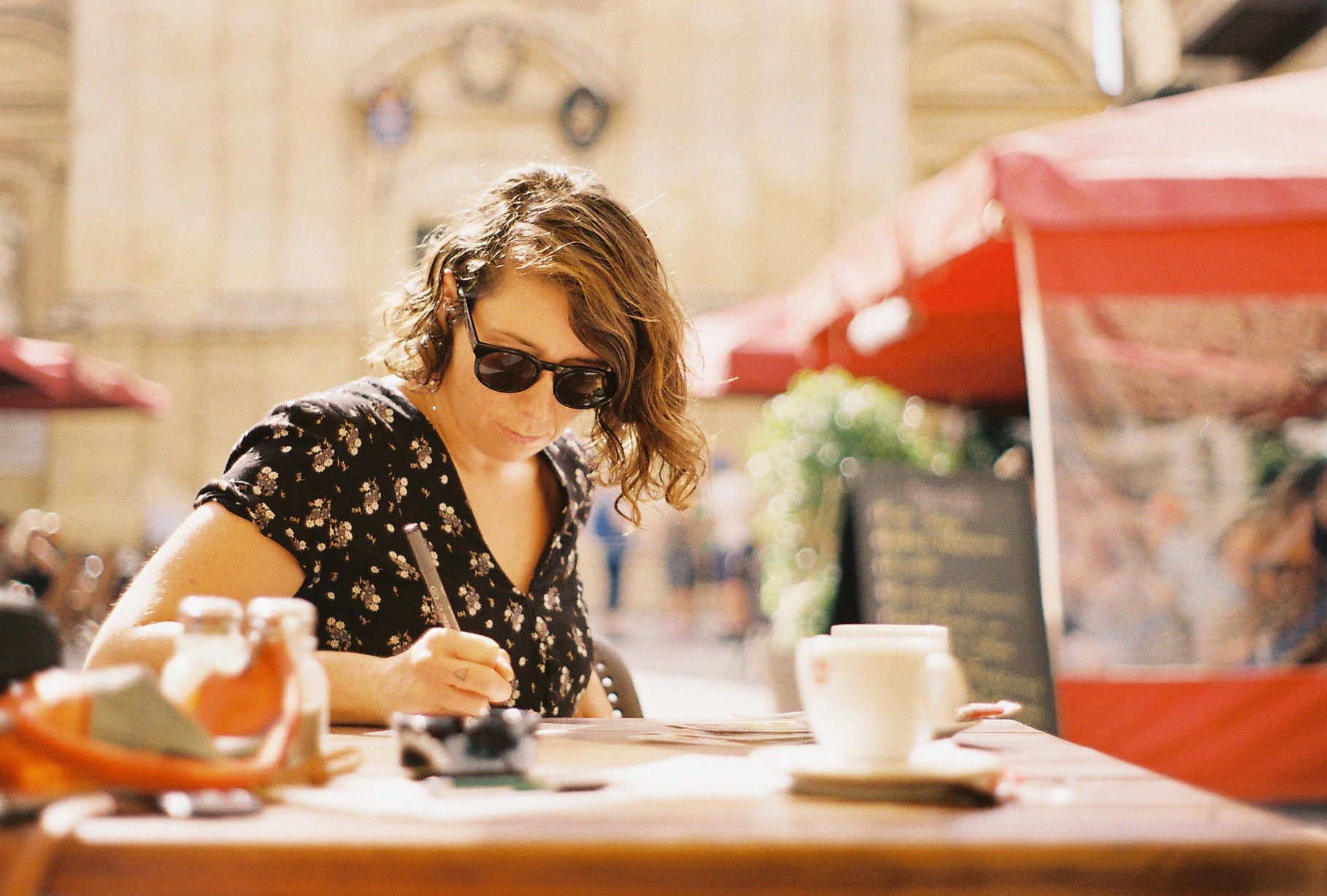 Harry having coffee and writing her postcards