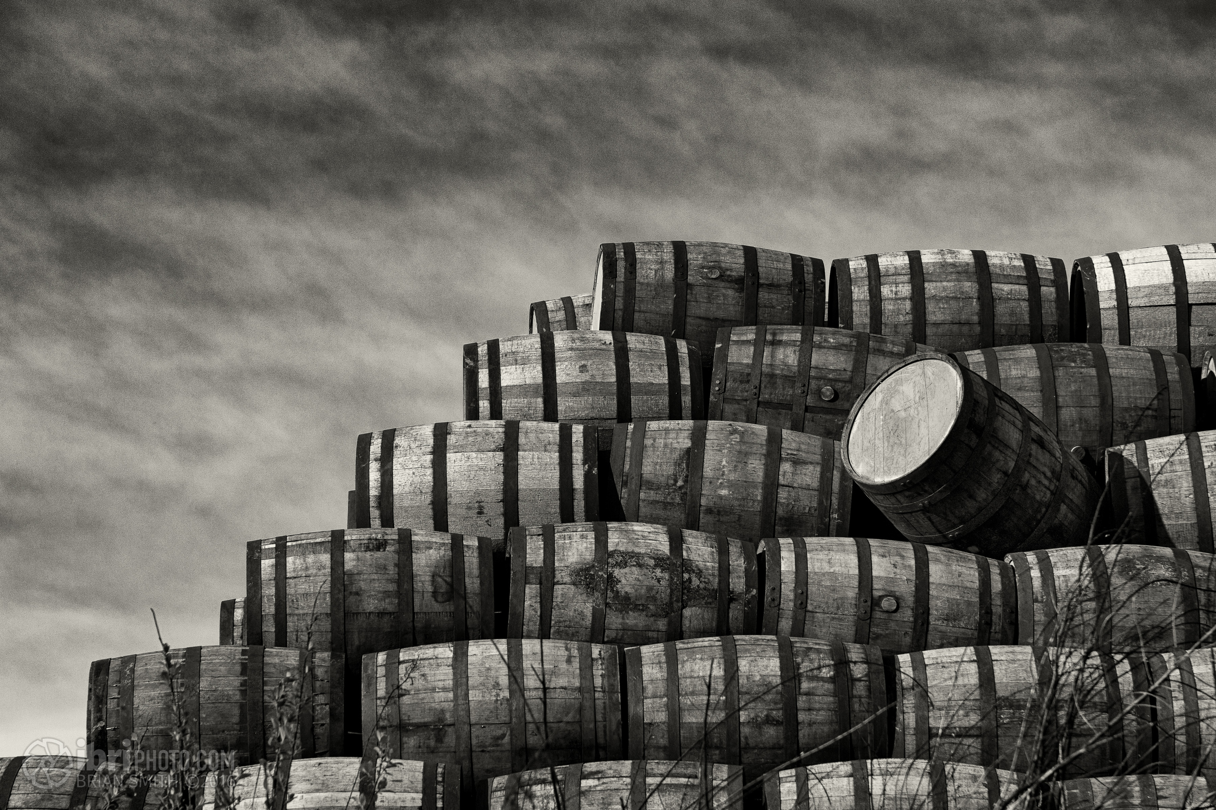 Stacks of whisky barrels, on the other side of a high fence, along the path that winds through the huge Diageo whisky bond.