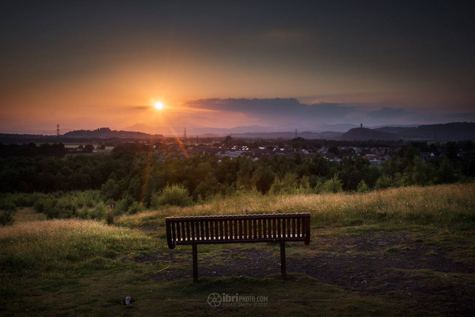 Sun setting beyond Stirling and the mountains of the Trossachs beyond. Perched on top of the, now nature reclaimed, colliery bing near one of the old eastern mining villages in the Stirling area.