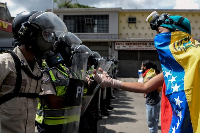 Venezuelan Opposition Protester confronts the Police