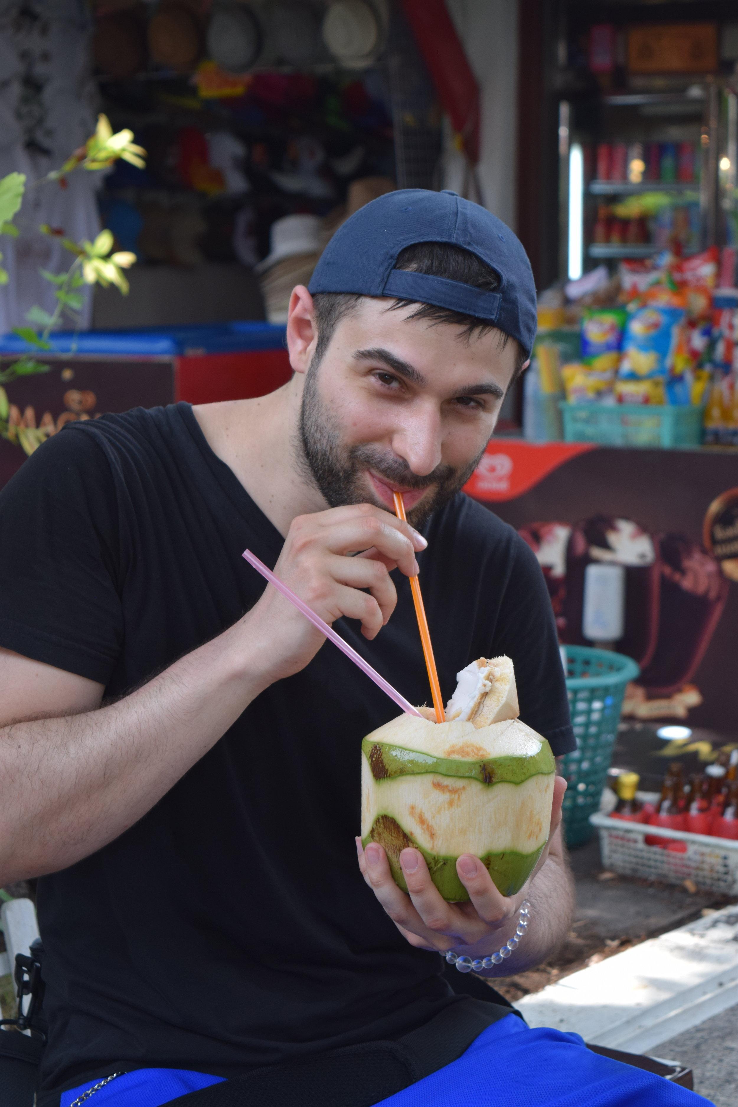 """""""Chilling""""mentre bevo succo di cocco in una rovente mattina thailandese."""