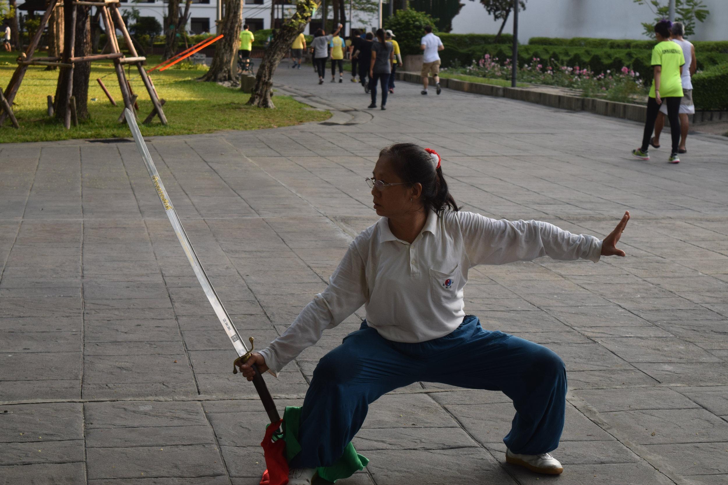 Questa nonnina sta praticando un'arte marziale cinese con diversi secoli di storia al parco pubblico di Bangkok. E quella spada è vera.Meglio non farla inca**are.