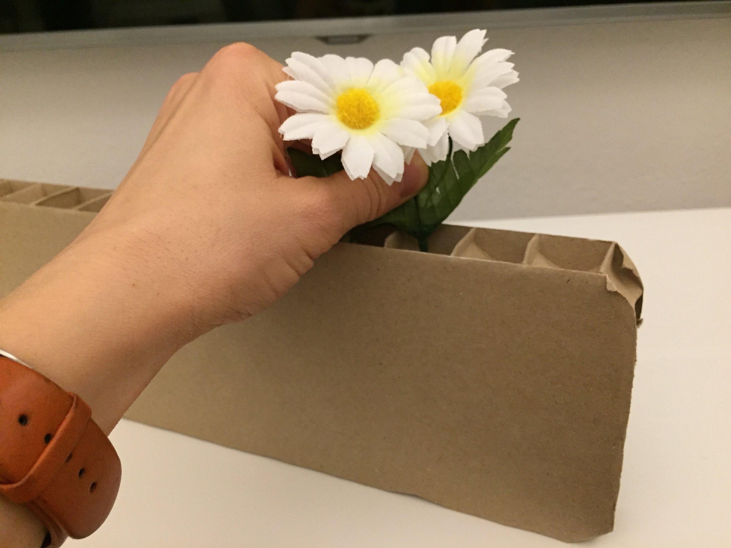 Pierced side of cardboard with plastic flowers.