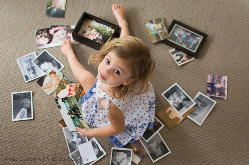 That watermark right there is another weeny lie - the photo credit for this image really belongs to my husband. This is our little girl surrounded by the family pictures she loves to look at.