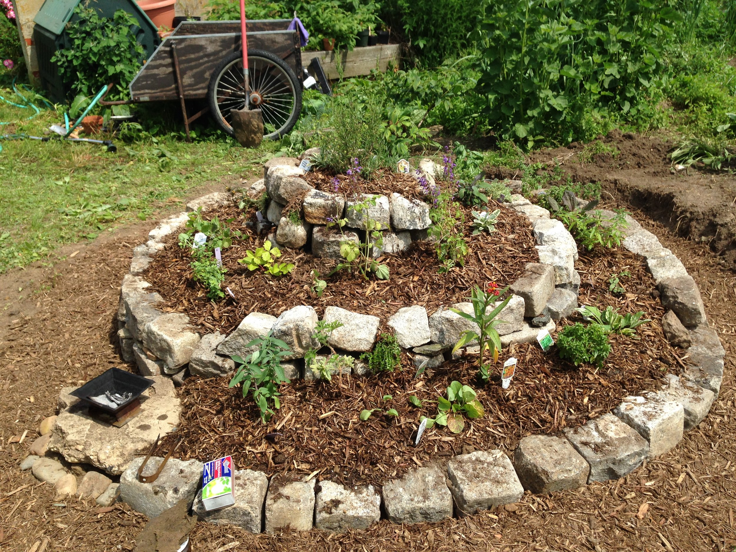 A Herb Spiral is a structure that creates microclimates in order to accommodate many plants in a small space.