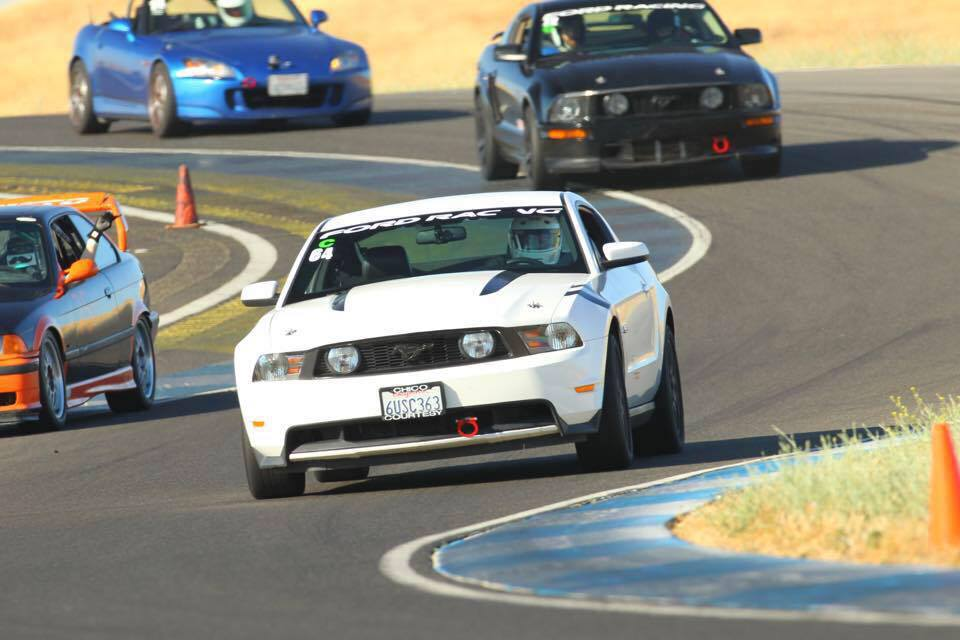 Dan being chased down in his white Mustang by his son Gerrit in his black Mustang at Thunderhill Raceway.