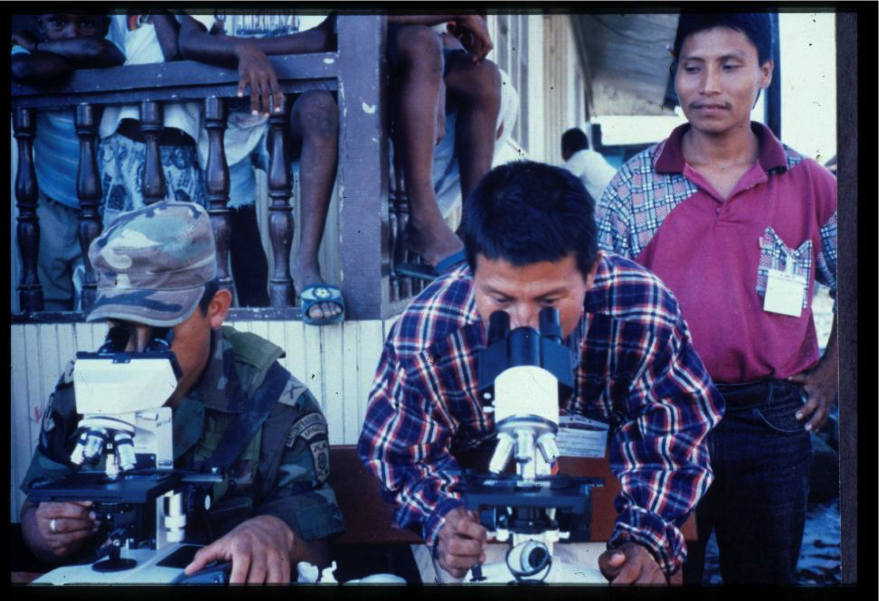 Our malaria workers examine a practice slide. A passing soldier wouldn't miss the fun