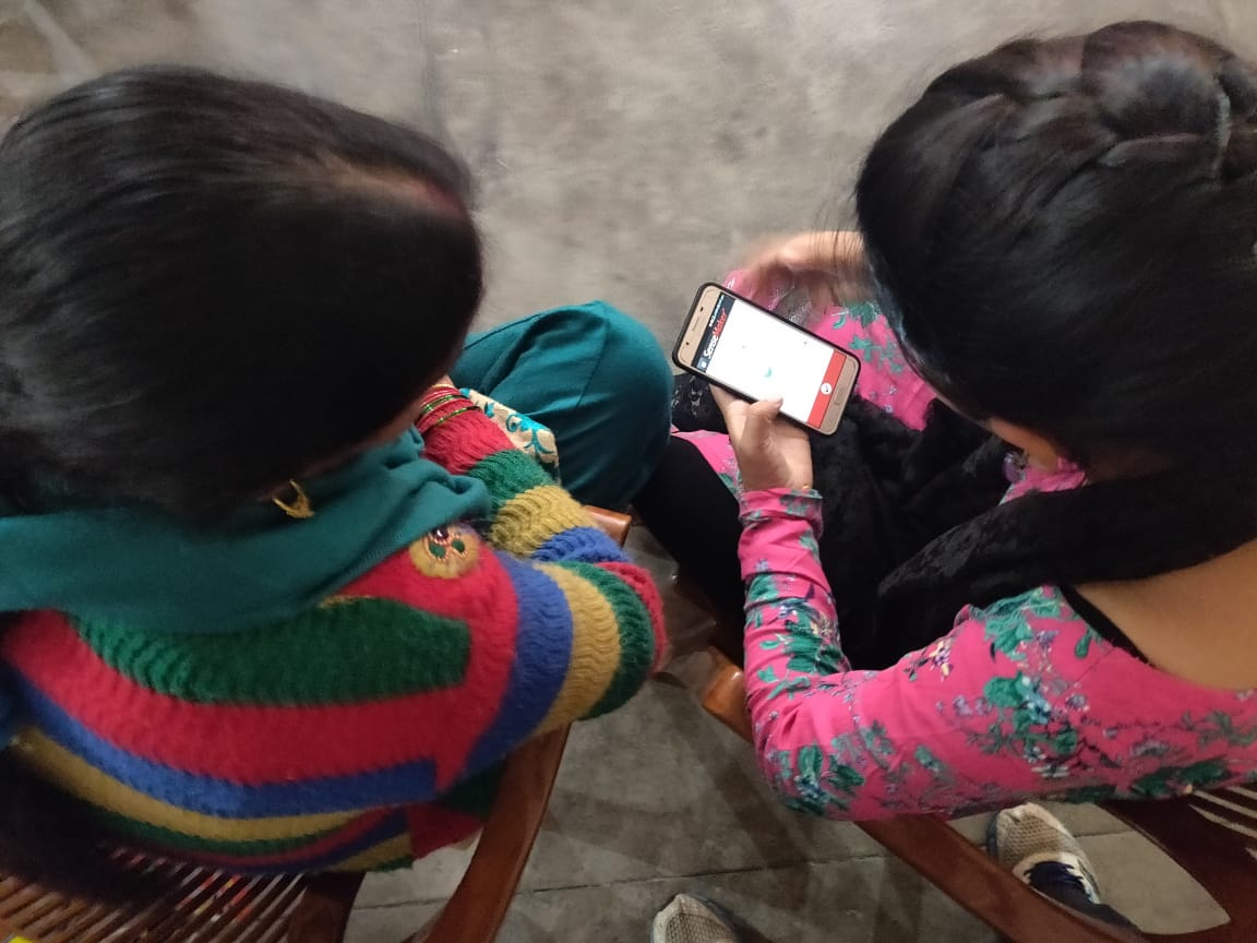 Making sense out of an app… Two of the community workers at a session to learn to use the app