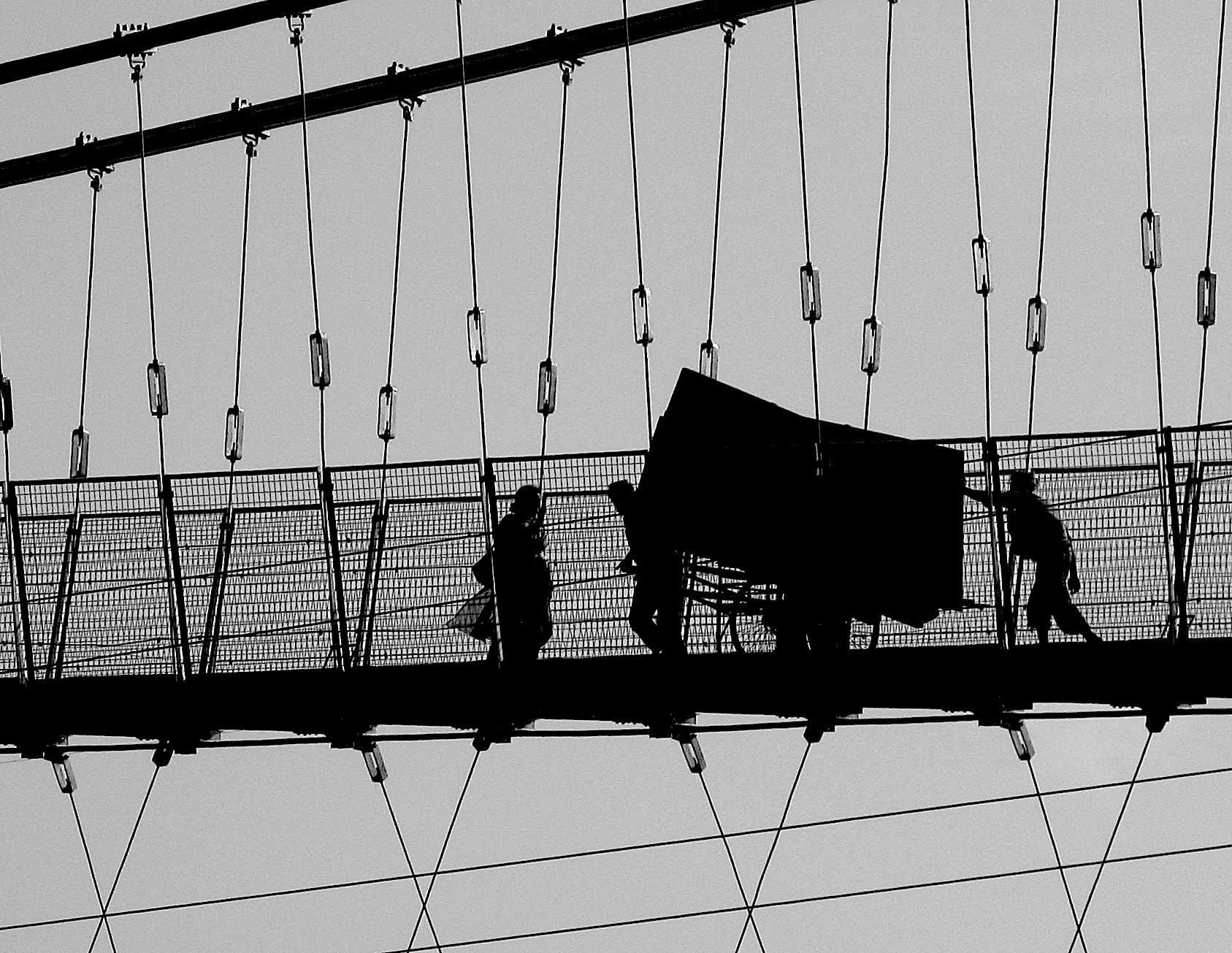 Hauling a handcart to Hell. Small government doesn't protect these faceless silhouettes' labour rights, their health their children's education, the sacred Ganges running polluted beneath the bridge…