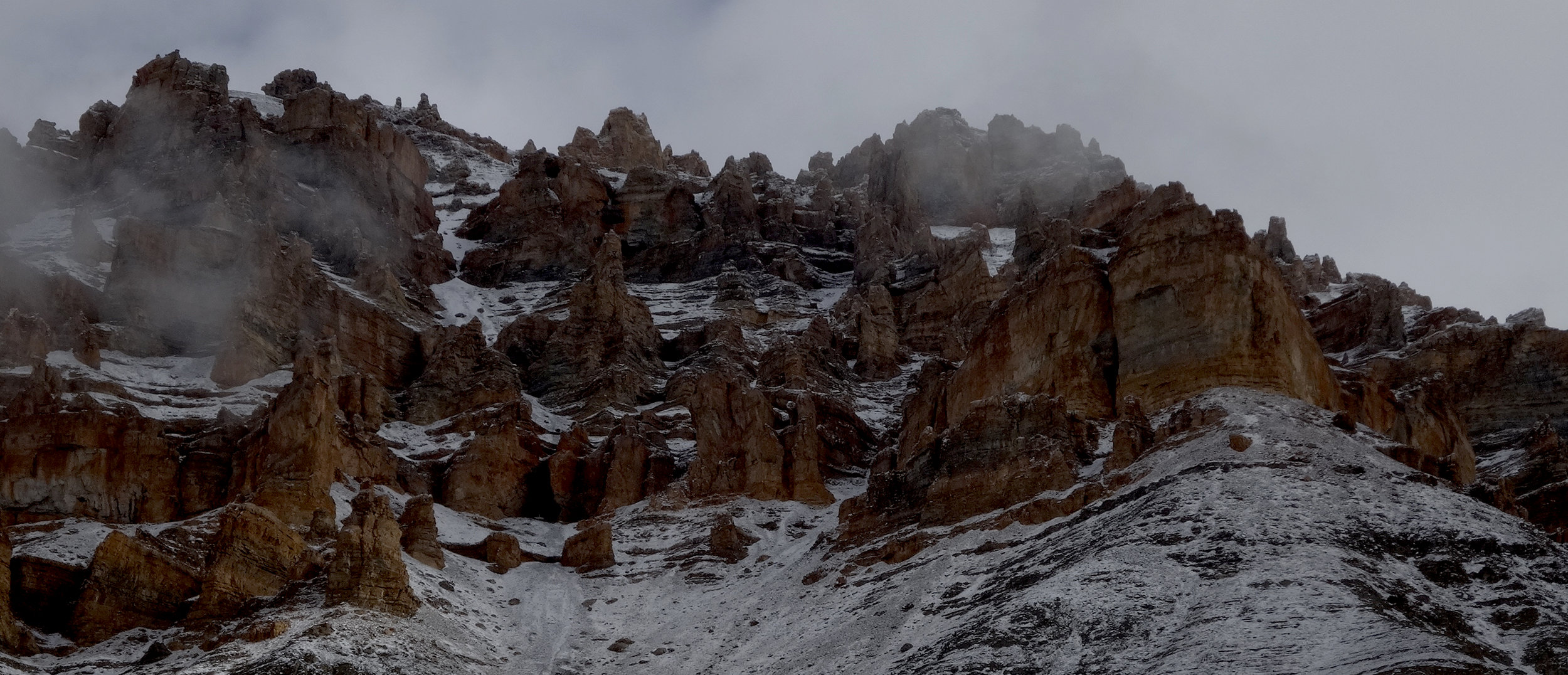 A crenellated canyon wall towers 2000m above us. Crossing the inner/outer divide to social solution spaces could be harder than climbing out through this.
