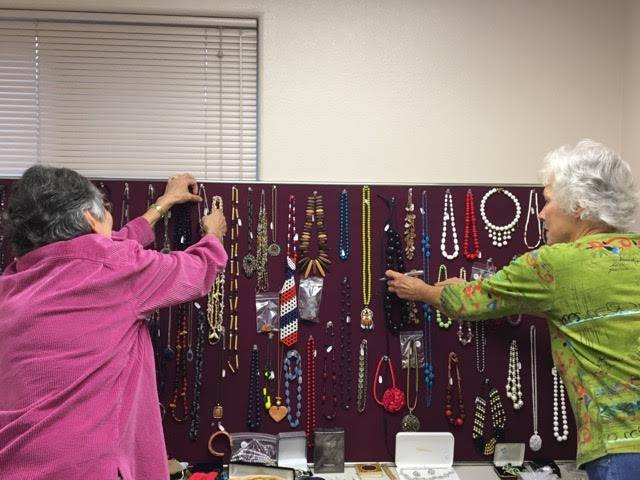 Volunteers set up jewelry for the annual jewelry sale at our Christmas Bazaar.