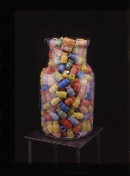 Spell Jar , 1999-2000: wax, blown glass, metal leaf, on steel stand; 58 x 10 1/2 x 10 1/2 inches. Tiny wax bottles have fragments of the word  abracadabra  on them.
