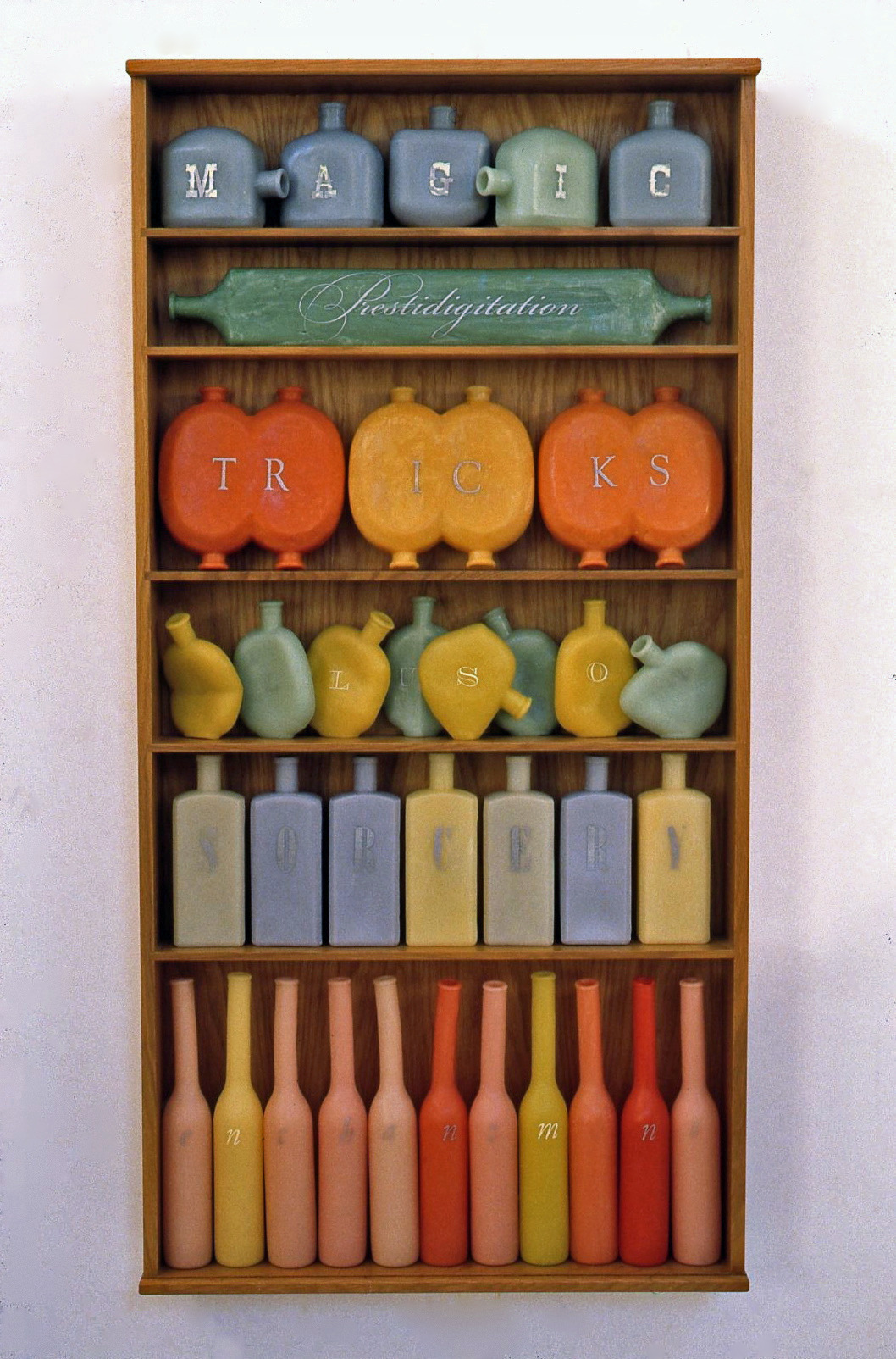Names of Magic,  2000: wax, wood, metal leaf, 54 x 27 x 5 1/2 inches. Each row of bottles spells one word. 