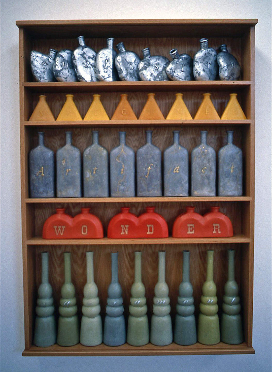 Museum,  1998: wax, applied metal leaf, wood; 44 1/2 x 31 x 5 1/2 inches. From top to bottom, the rows of vessels read: curiosity, specimen, artifact, wonder, sacrament.