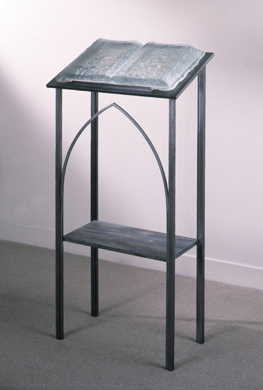 Witness , 1995: cast glass, rolled colored glass with sandblasting, steel; 52 x 17 x 14 inches.  The text visible through the glass book says  forgive ; sandblasted into the glass shelf below is  remember  .