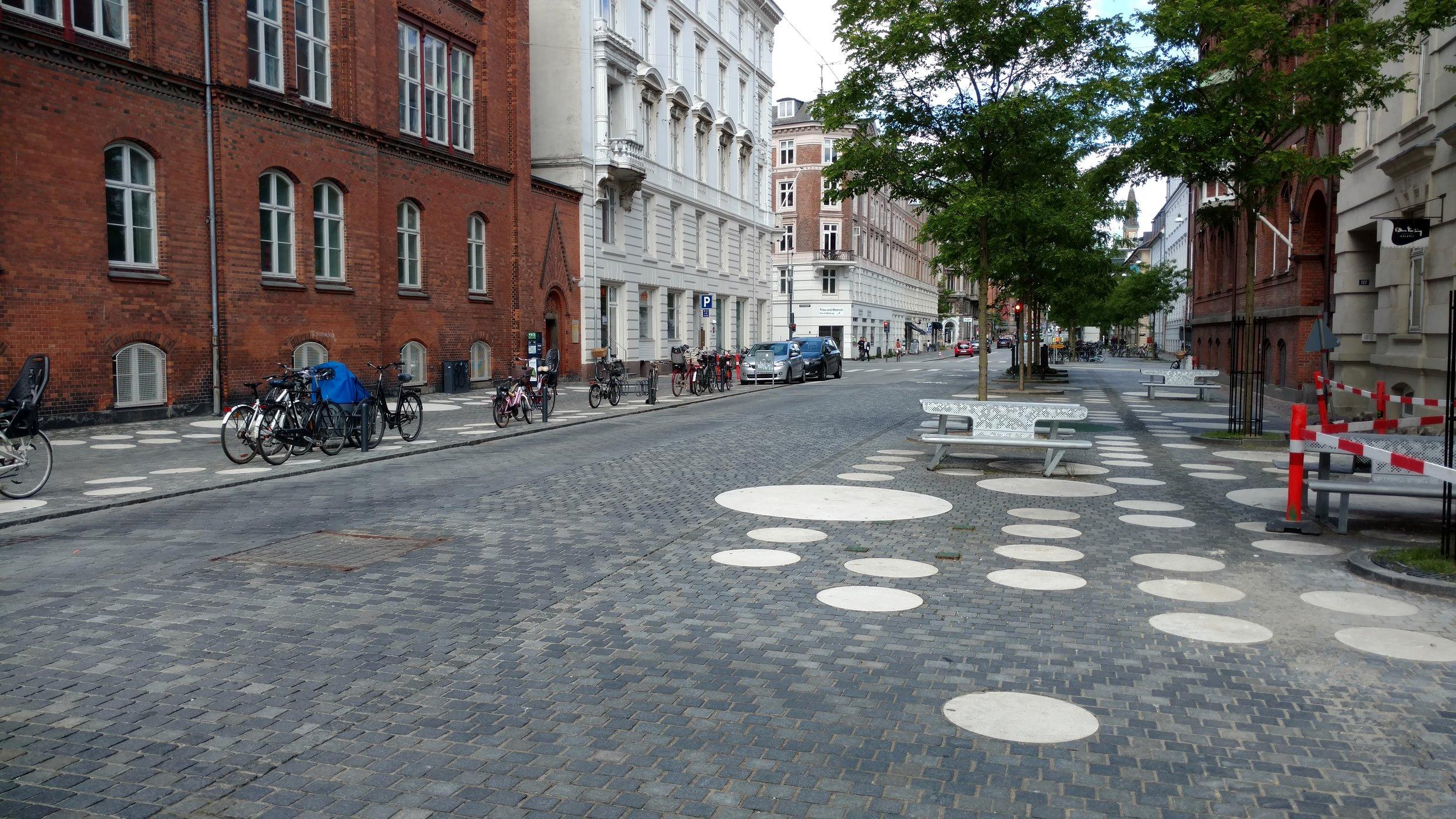 Wide sidewalks and public space outside a school.