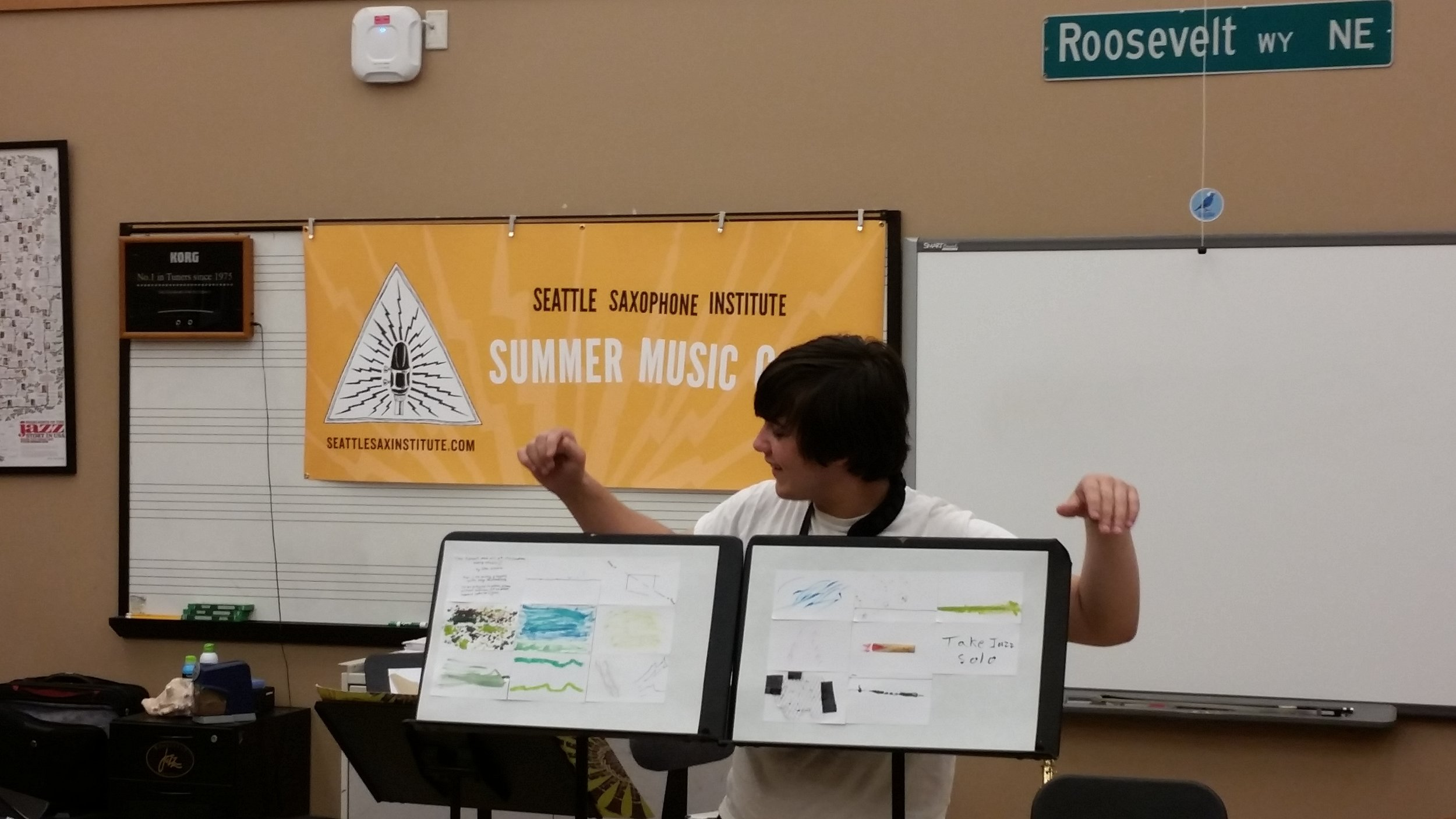 "A summer 2016 High School camp attendee displays his ""Graphic Score,"" in which he used found materials from around his house to create a visual composition for the ensemble."