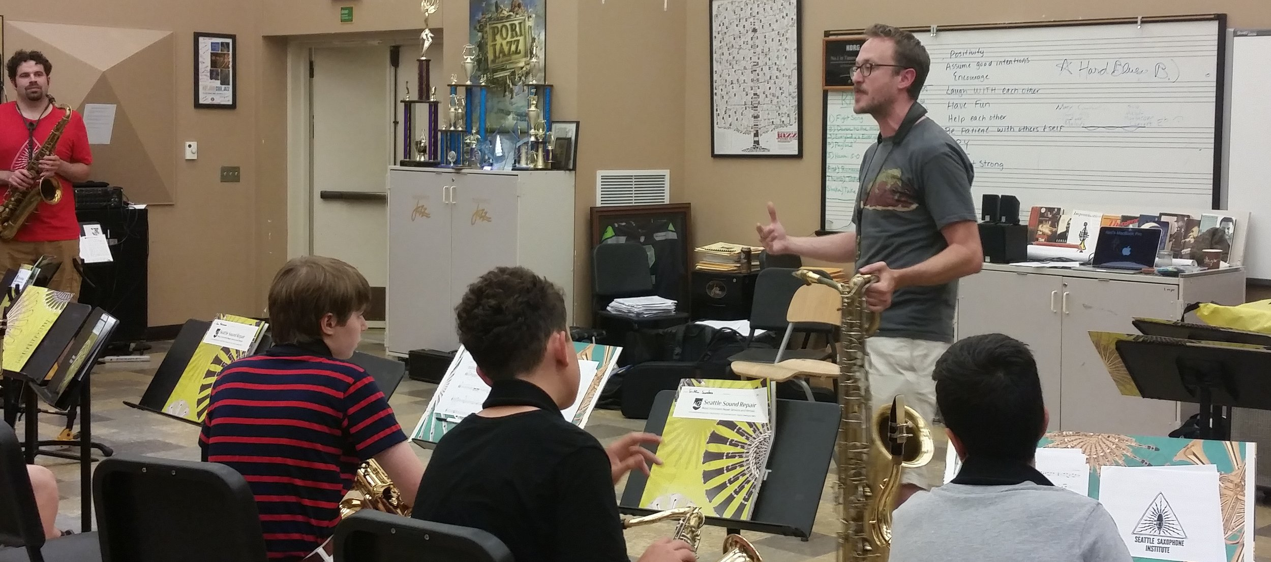 Guest artists Peter Daniel teaches students about traditional brass-band music at the High School camp while coach Steve Treseler looks on.