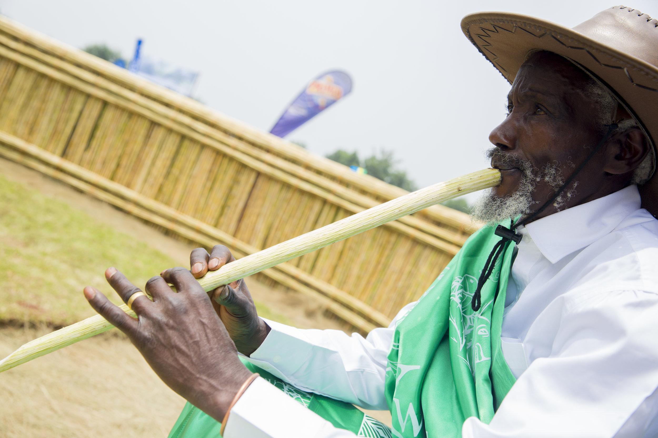 An elderly man playing a flute.