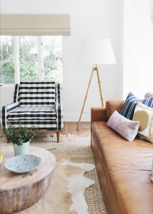 Layered rugs add awesome texture to a bright and airy  living room  by Studio McGee. And we love us some buffalo check on that chair!