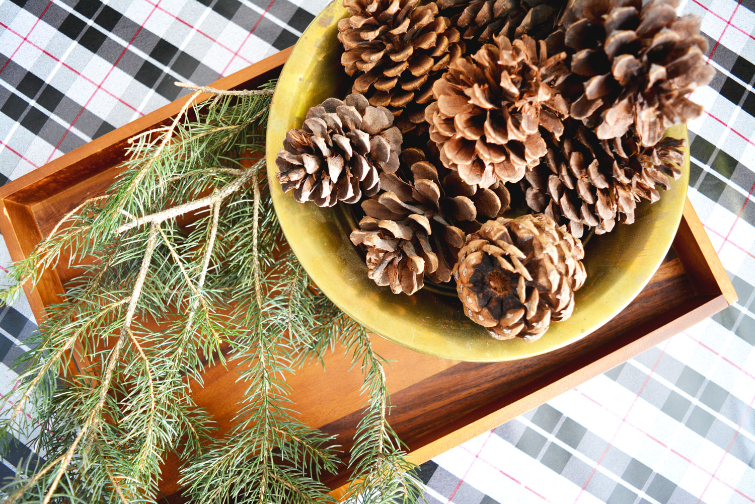 Add a sprig of fresh greenery to a simple wooden tray for some casual Christmas style.