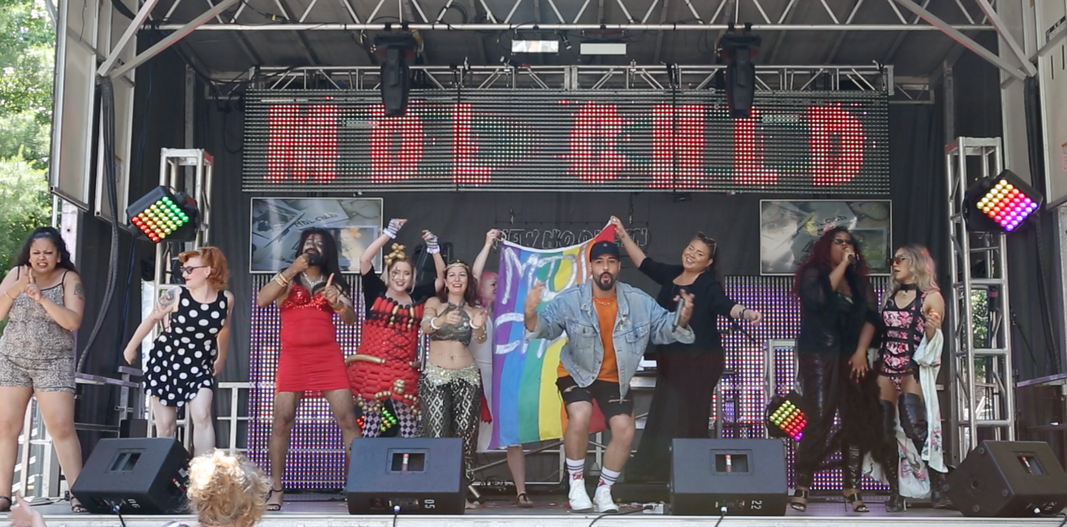 Toronto Pride 2019  Left to Right: Gaitrie (Deaf, Guyanese, ASL Performer), Knox (Burlesque performer [Visual performance piece for Deaf community]), Jaideep (Gay, Deaf, Indian, ASL Performer), Bella Magic (Circus Performer [Visual]), Stacie Noel (Circus Performer [Visual]), MDL CHLD (Christopher Corsini, Gay performer/ASL Interpreter), Ashley Bomberry (Queer, Indigenous, Activist/Speaker/Creator), Amanda Mae (Bajan, Female Vocalist), Vachina Dynasty (Filipino/Chinese, Queer Drag Queen)  Out Of Frame: Rogue Benjamin (Queer, Indigenous, ASL Interpreter [ground level providing access & supporting the Deaf performers]), 2 BIPOC Queer dancers holding Advocacy signs, 2 lesbian caucasian dancers holding Advocacy signs.