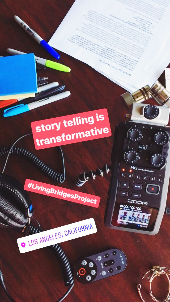 "[Photo from above of part of a wooden table filled with recording supplies such as an audio recorder, a remote, headphones and various papers and markers. The words, ""storytelling is transformative"" and ""#LivingBridgesProject"" are written in white in red boxes over the photo and a geo tag of ""Los Angeles, California"" is in white. Photo by  MM .]"