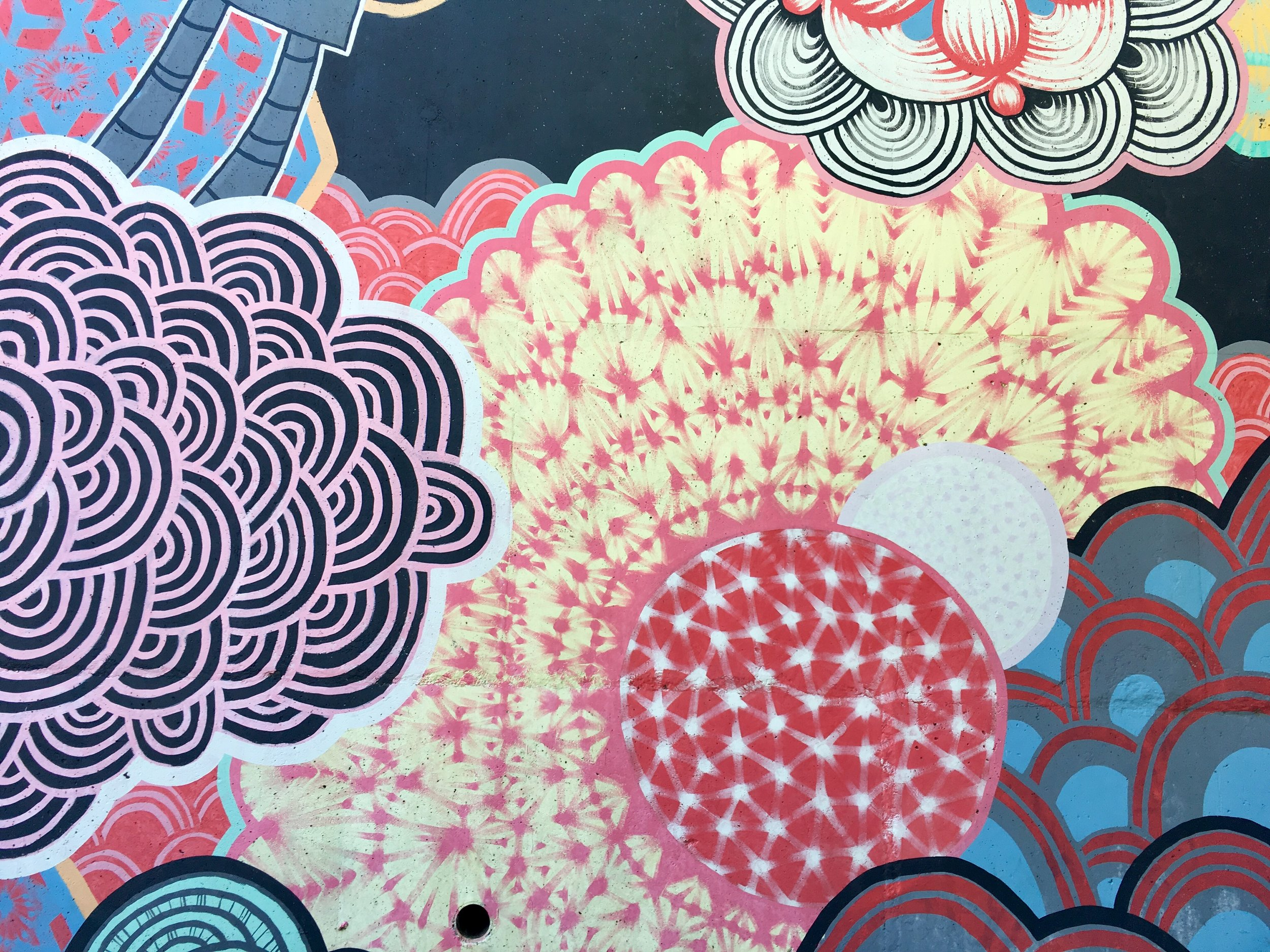 [Photo of a mural in Atlanta filled with abstract flower-like shapes in pinks, reds, blues, blacks, whites and mint green. Photo by  MM .]