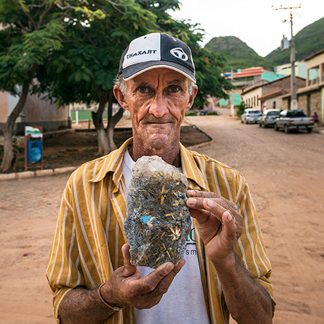 Figure 2. A local miner holds up an example of the golden rutilated quartz found in the Remedios area. Photo by Robert Weldon/GIA.