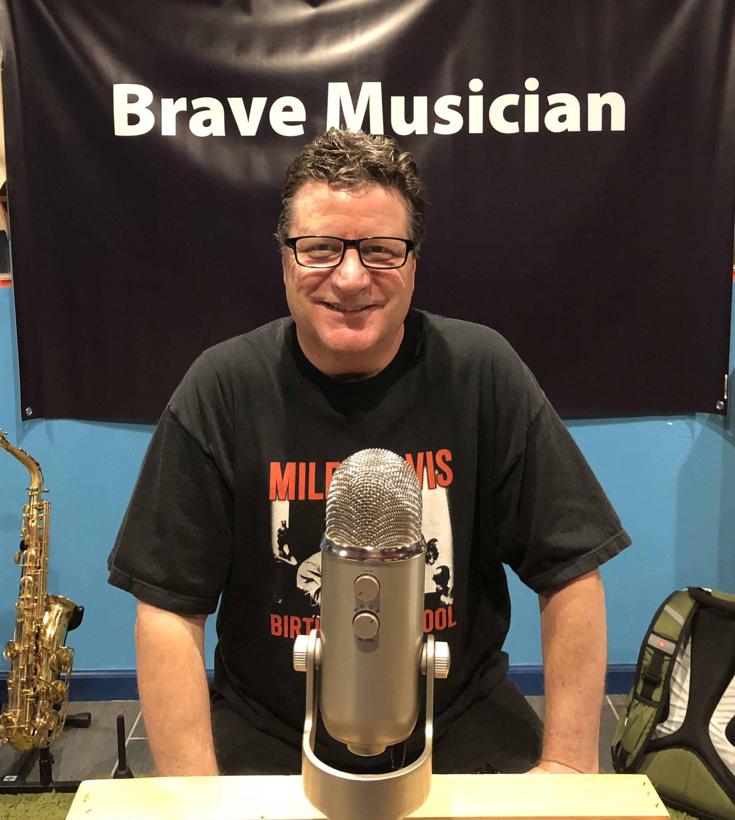 Chuck Curry smiling for the camera in front of the Brave Musician banner in Monica's music studio.