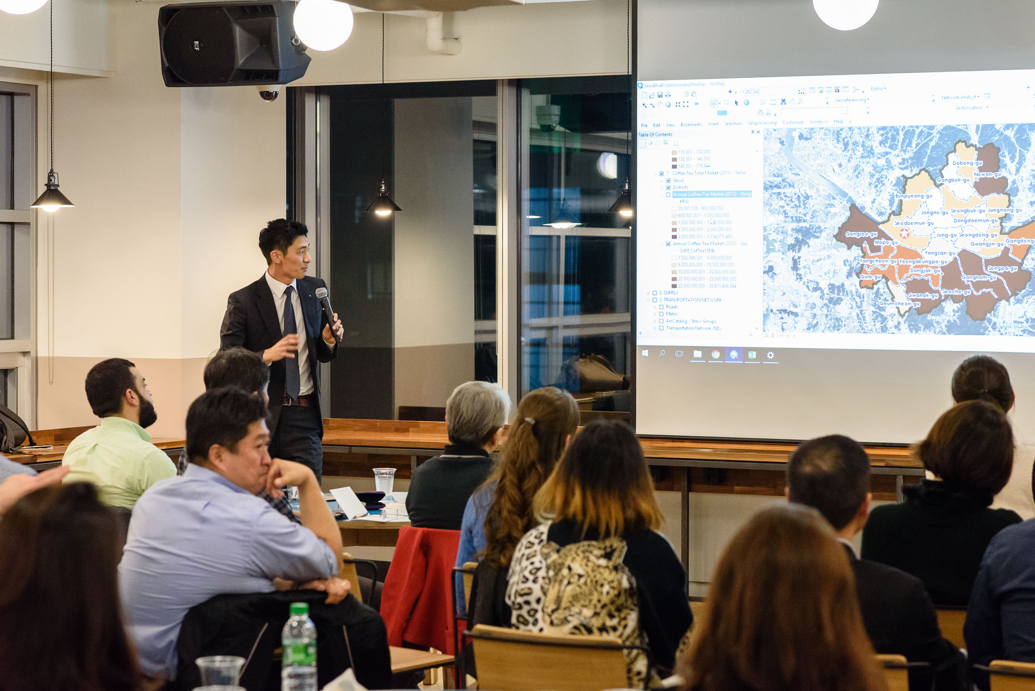 Raymond referring to a graduated color map in ArcGIS showing total coffee and tea sales by district for 2015. The darker areas represent districts with high coffee and tea sales. (Photo by Cristian Bucur)