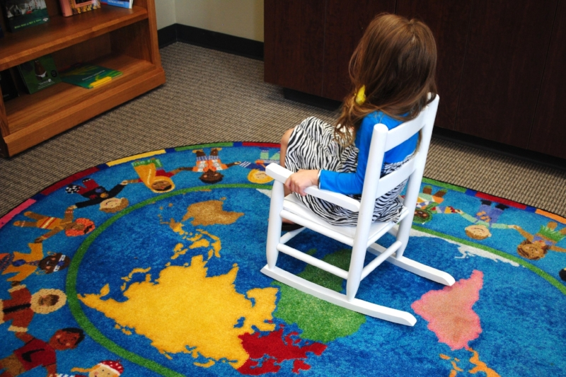 A little girl relaxes in Domestic Violence Intervention Services (DVIS)'s library during the April 2016 dedication ceremony.