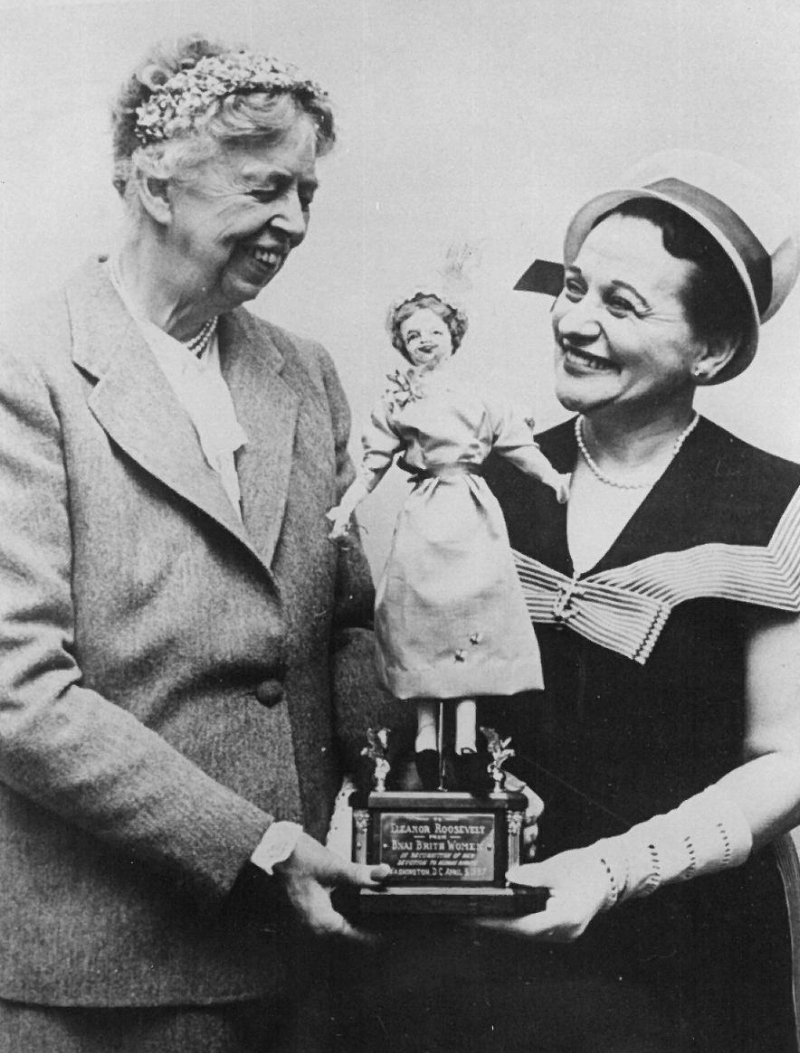 In 1958, former First Lady Eleanor Roosevelt accepts a Doll for Democracy from Anita Perlman, president of B'nai B'rith Women which later became JWI. The doll was part of the organization's nationwide program for schoolchildren to promote tolerance and understanding between individuals of different backgrounds.
