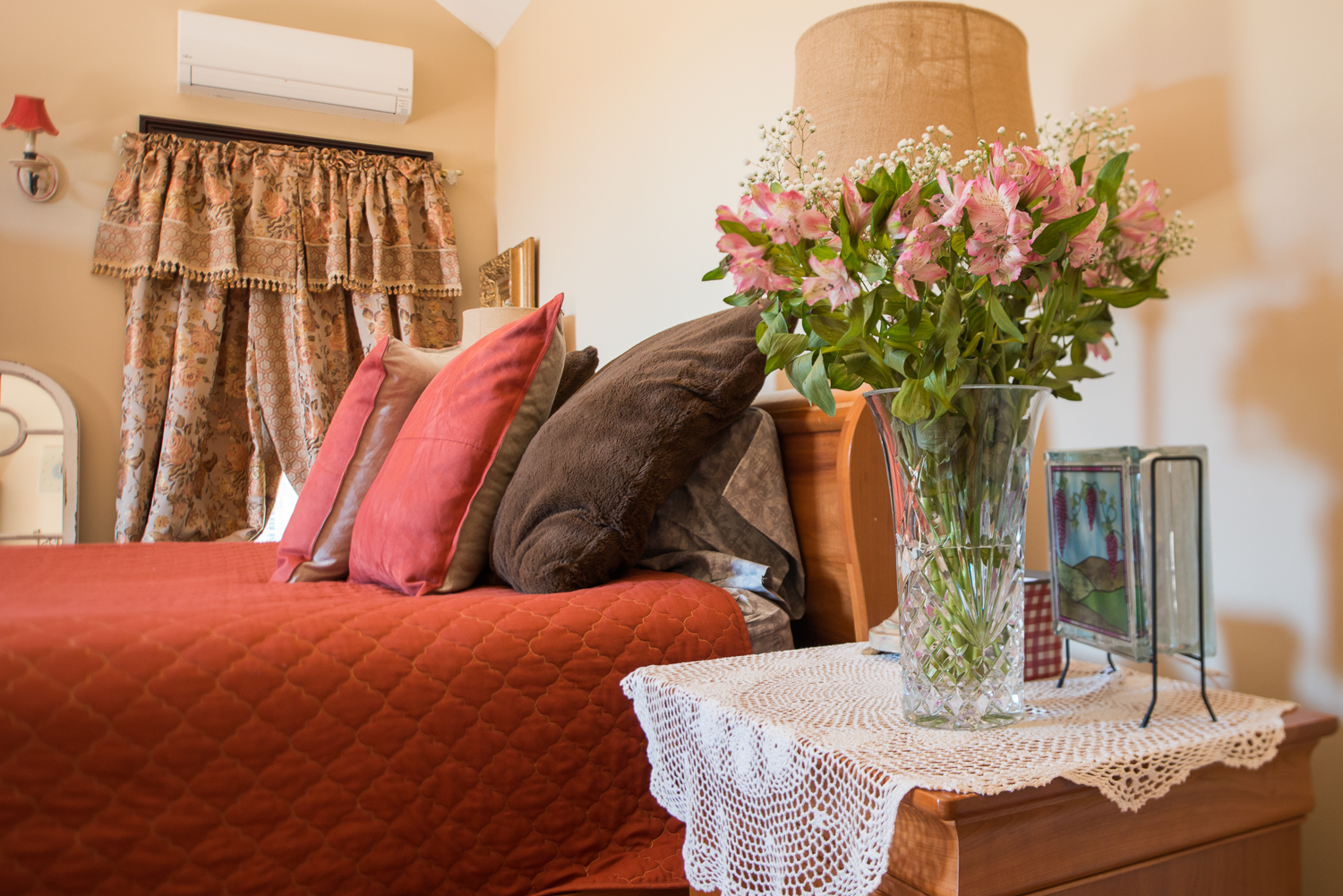 pillows on a bed with flowers on table