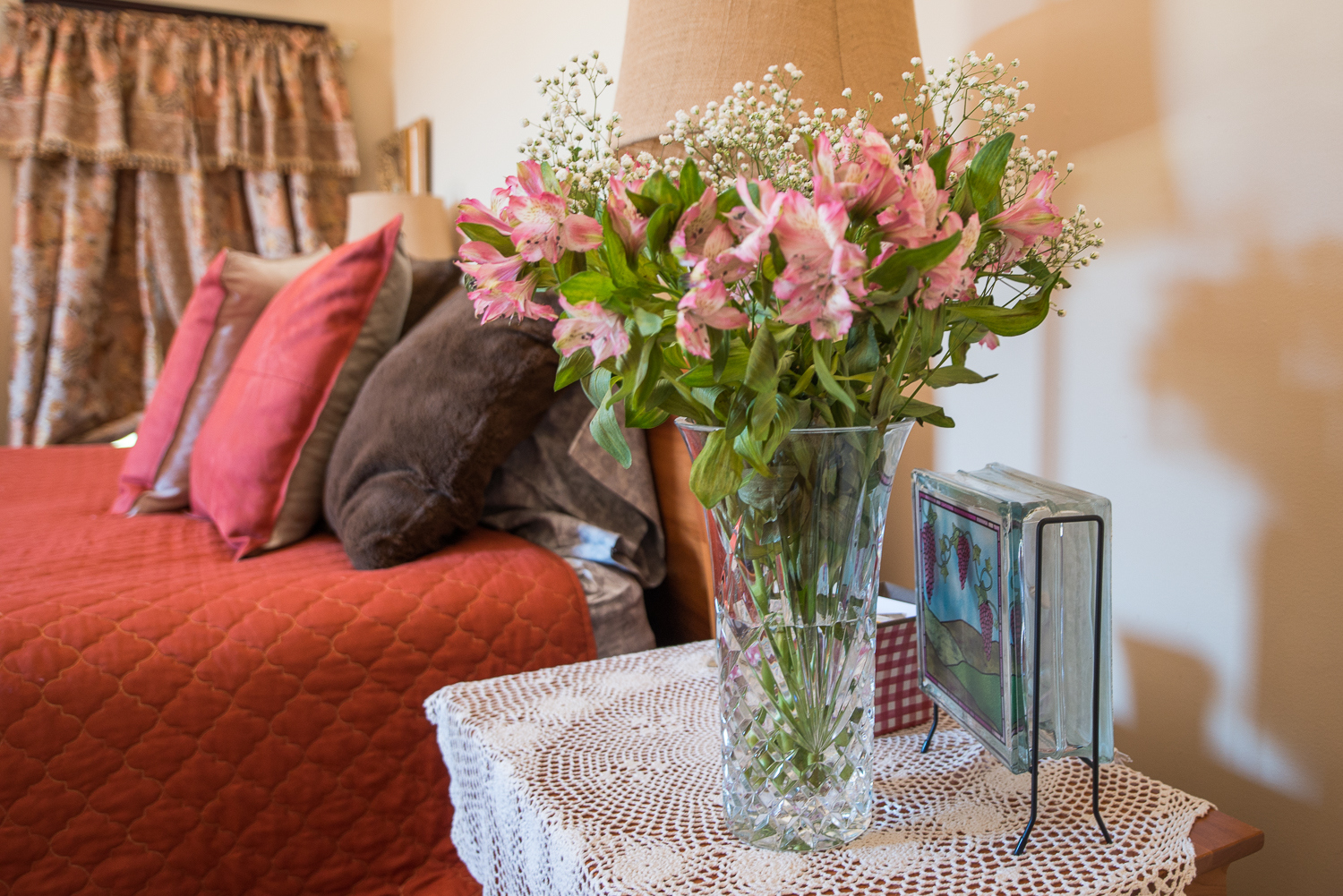 flowers on table with bed in background