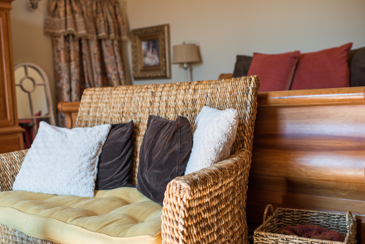 chair with pillows next to a bed