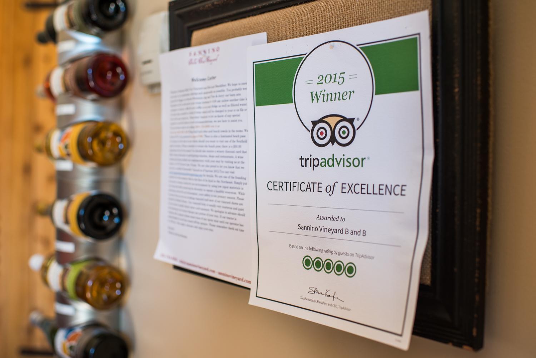 trip advisor winner certificate on wall with wine bottle in background