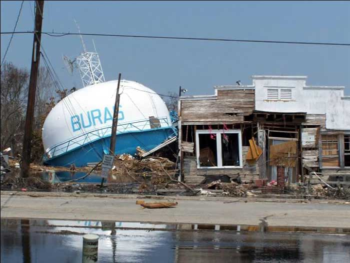 """Post   Hurricane Katrina  photo. Fallen, elevated water tower and smashed building in Buras, Louisiana, where landfall occurred at 6:10 a.m. CDT on August 29, 2005. US EPA photo from """"http://www.epa.gov/katrina/images/Slide9.jpg"""" by the United States."""