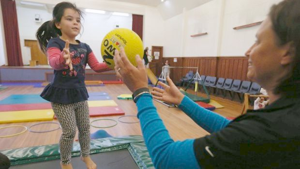 Jenny Dravitzki, left of Sport Tasman throws a ball to Quayde McIntyre, 4, at the Toddler Better Health Programme at the Richmond Town Hall.